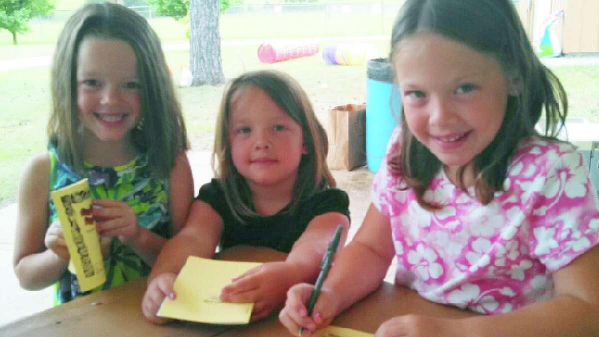 Reading together: Three children participate in the June 22 kickoff event for the Reed City Library's Summer Reading Program at West River Park. (Courtesy photo)