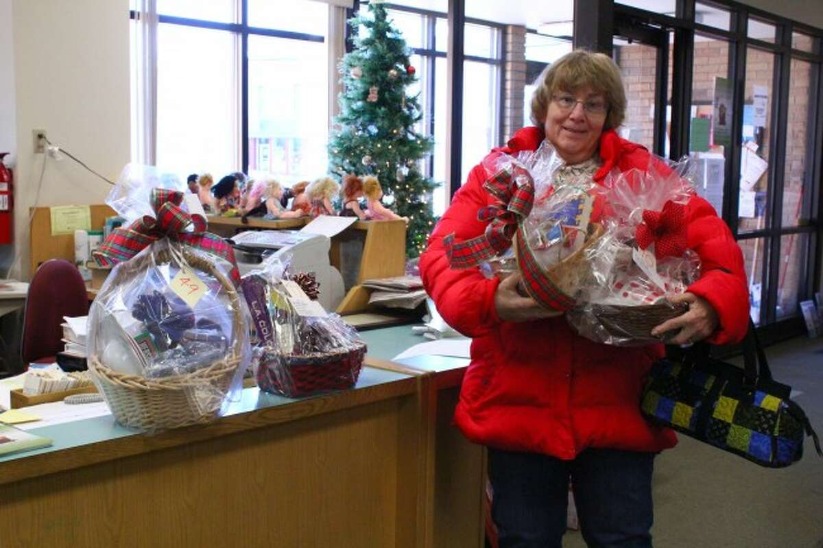 WINNER: Bonnie Hoke of Evart stands with four of her baskets she won during the auction event. Hoke participates in the event every year and enjoys the bidding wars.