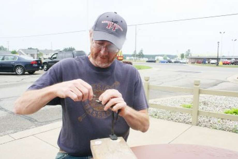 FLY FISHING: Evart's Andy Duffy ties a fly to get ready for more fishing. (Herald Review/John Raffel)