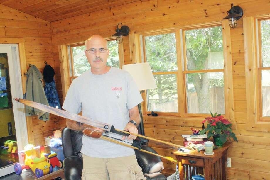Hunting season: Jeff Junker gets his bow ready for next season. (Herald Review/John Raffel)