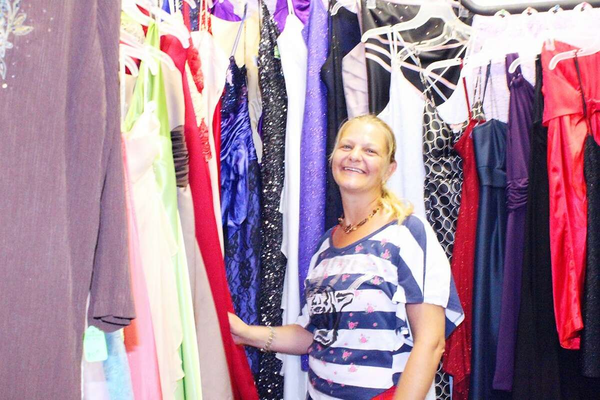 A POSITIVE PRESENCE: Unique 4 U owner, Rachel Strobel, stands next to the formal dresses she has in her store, located at 226 N. Main St. in Evart. The second-hand clothing store opened almost three months ago. Strobel said she wants her to be involved in the community and give back.(Herald Review photo/Emily Grove-Davis)