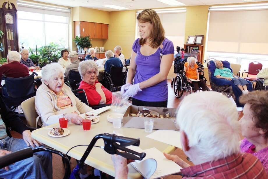A baked gift: Spectrum Health Reed City Hospital Activities Coordinator Heather Juengel helps serve large pieces of the oversized donuts to a group of seniors who are excited to receive the gift. (Herald Review photo/Karin Armbruster)
