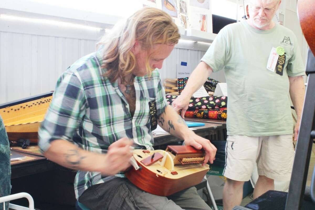 MYSTERIOUS MELODIES: Michael Opp plays the hurdy-gurdy while his friend, Mel Doories looks on. Doories' business, Hurdy-Gurdy Crafters, makes the unique instrument many people have never heard or heard of. (Herald Review photo/Karin Armbruster)