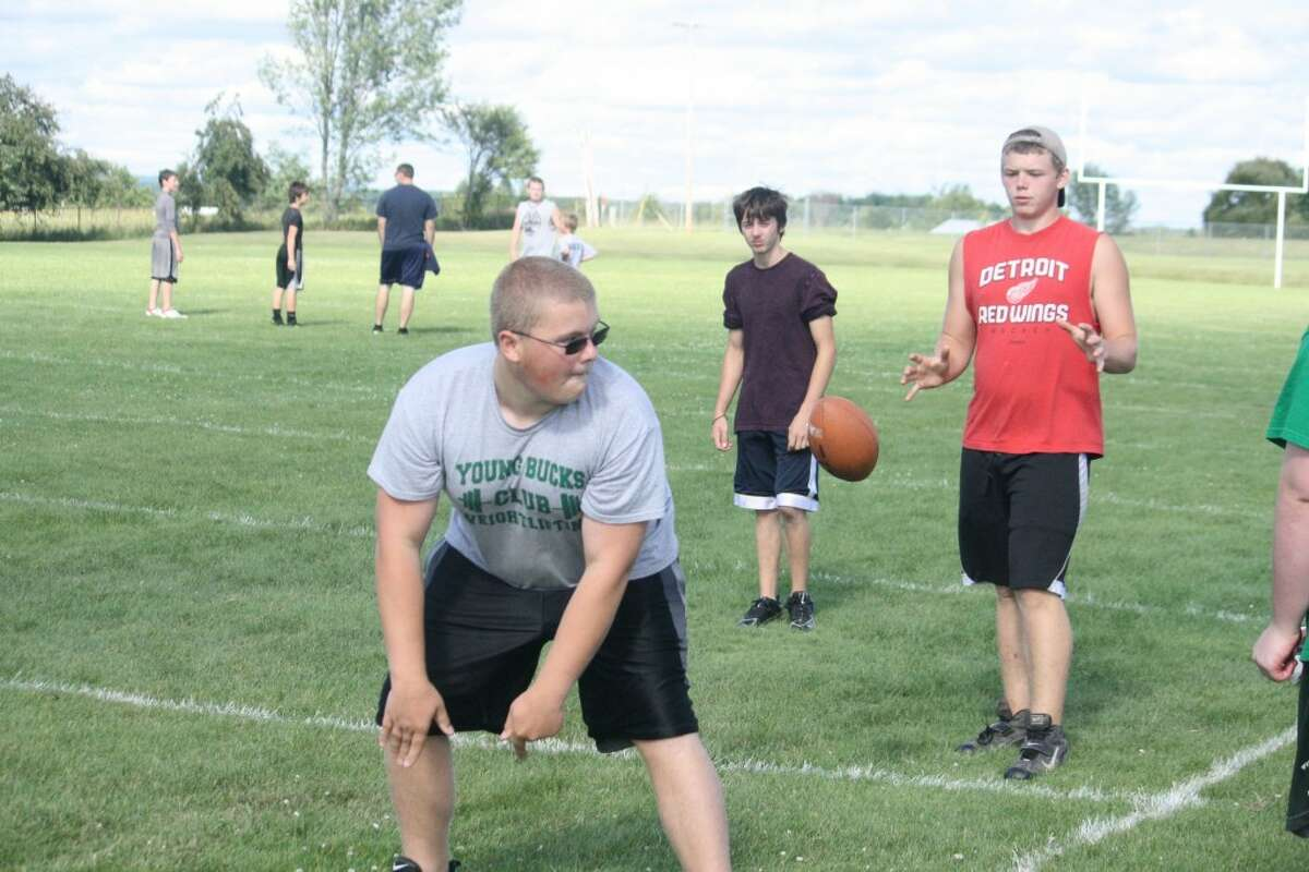 Football practice: Pine River's Brady Loop (from) and Josh Jackson, both sophomores, work on their snap exchanges Monday during the Bucks football camp.