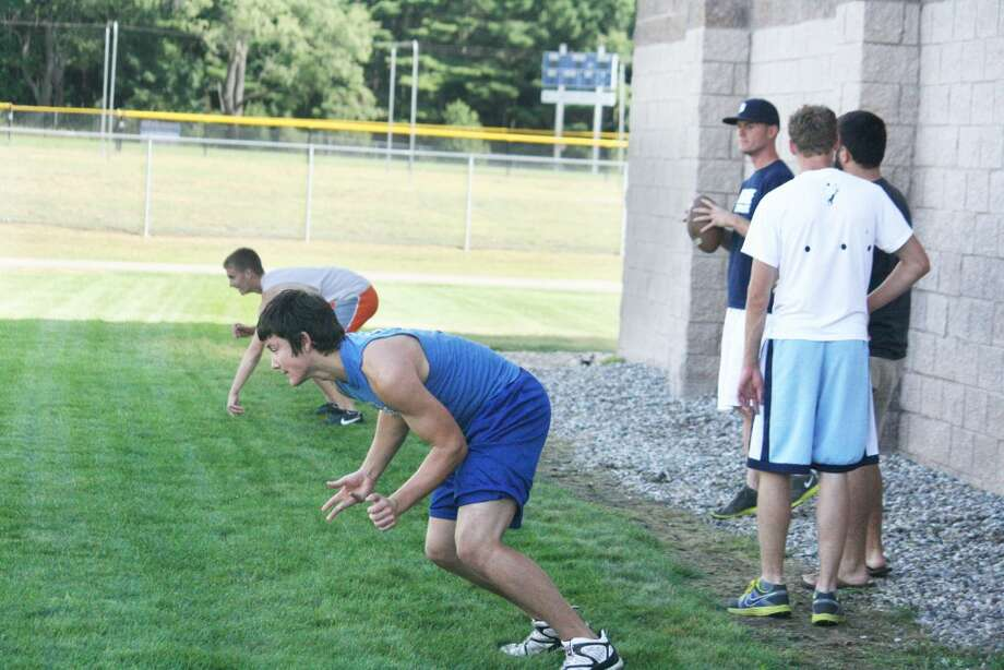 summer practice: Evart football players and coaches work on pass routes Monday morning. (Herald Review/John Raffel photo)