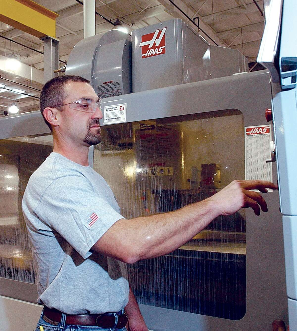 A machining supervisor programs a vertical machining center at the Middletown aerospace manufacturer Pegasus Manufacturing Corp.
