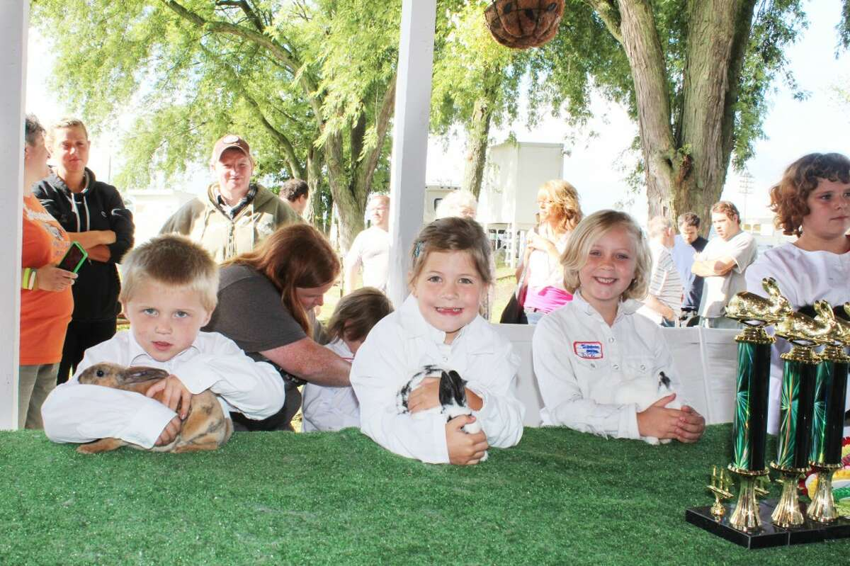 RABBITS: Future 4-H members show their rabbits on Monday at the Osceola County 4h-FFA Fair in Evart while smiling for the camera. (Herald Review photo/Karin Armbruster)