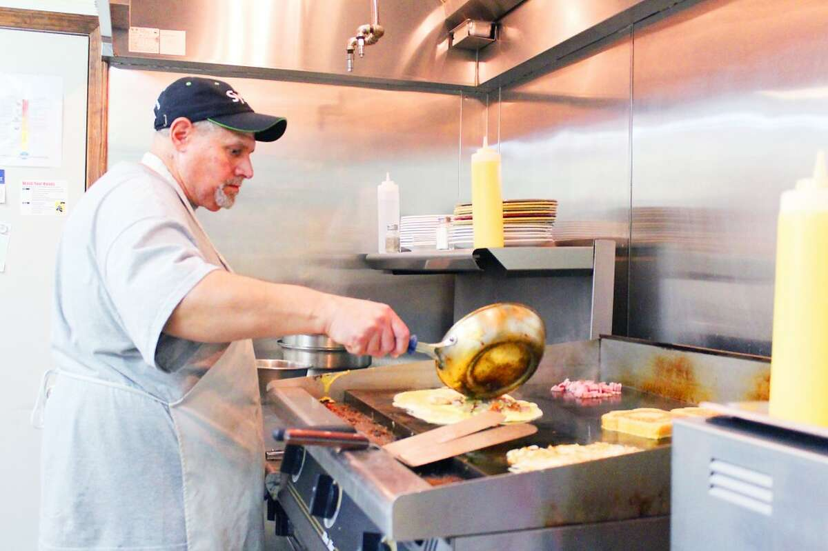 Omelet: Richard Pemberton, one of the owners of All American Cafe in Evart, prepares the 'Kitchen Sink' omelet on a flat-top grill. Pemberton and co-owner Shari Holben expanded their restaurant business from Nestle Inn Cafe in Reed City. (Herald Review photo/Karin Armbruster)