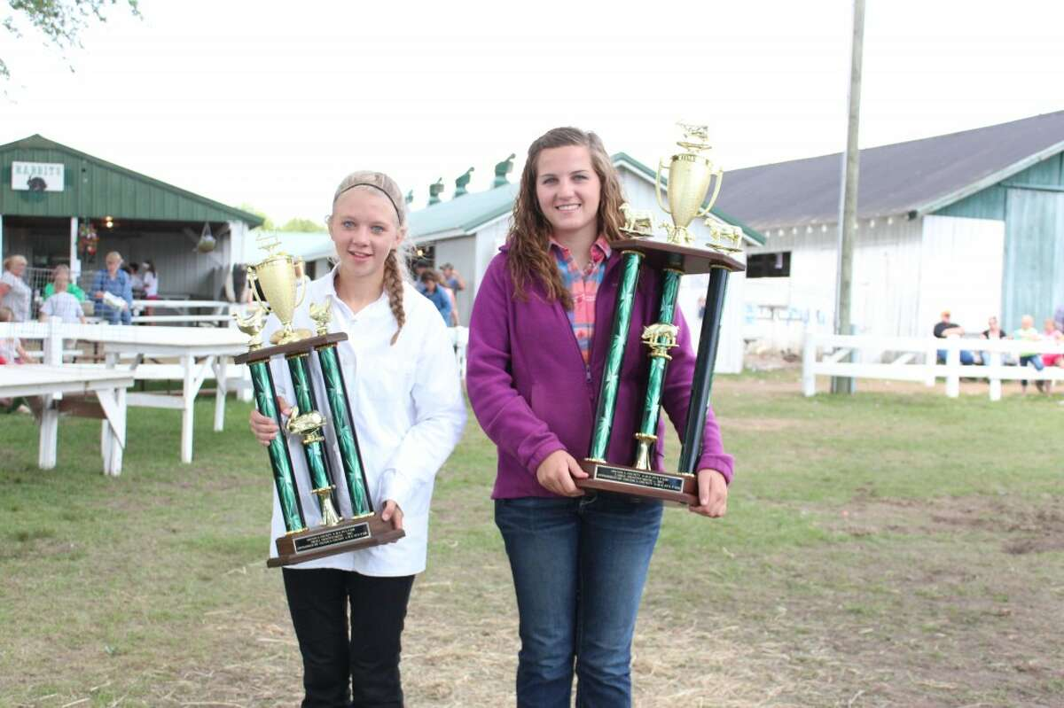 4-H winners: Emily Ruppert (left) and Morgan Cook pose with the trophies they received after they won the Sweepstakes Showmanship competition for small and large animals at the 2013 Osceola County 4H-FFA Fair. (Herald Review photo/Karin Armbruster)