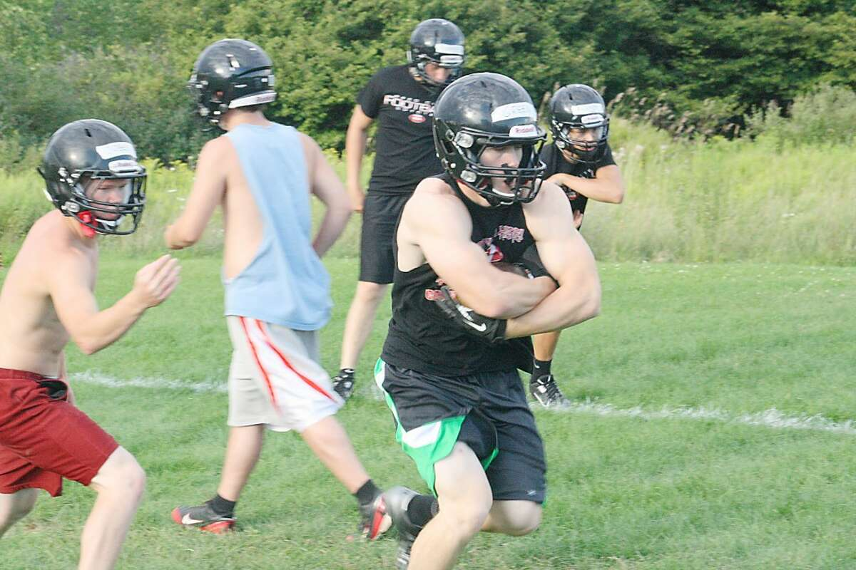RUNNING DRILLS: Jon Green of Reed City takes the football during a drill Monday night. (Herald Review/John Raffel)