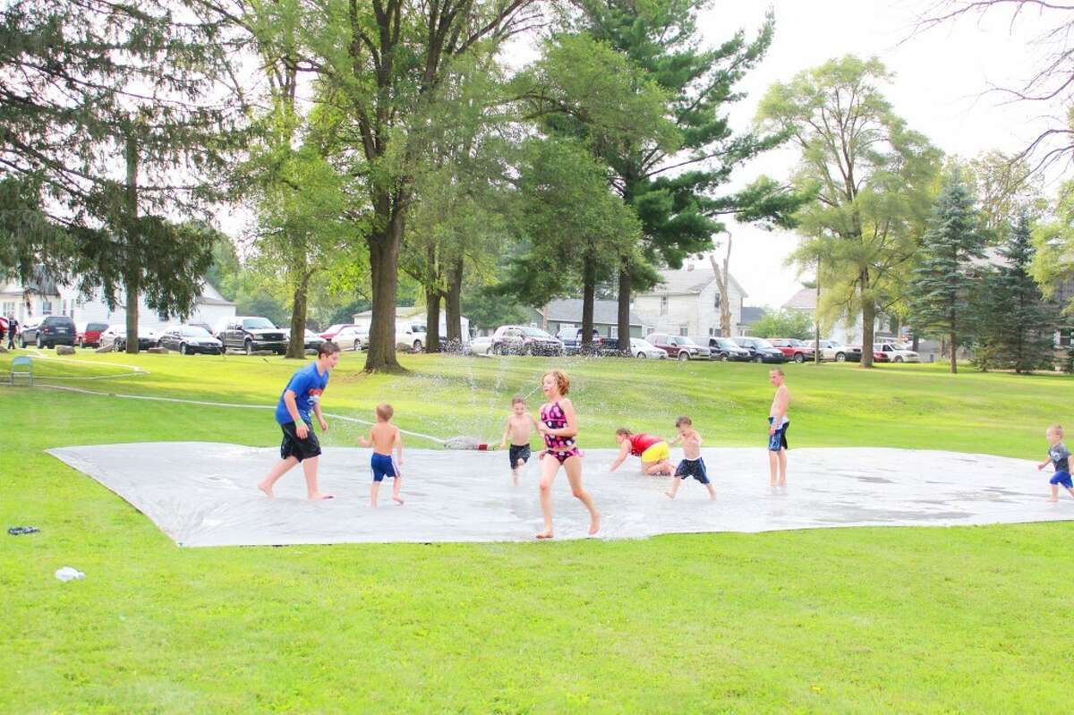 slip and slide: Kids play in the sprinkler on a large splash pad set up by the Evart Fire Department. (Herald Review photos/Karin Armbruster)