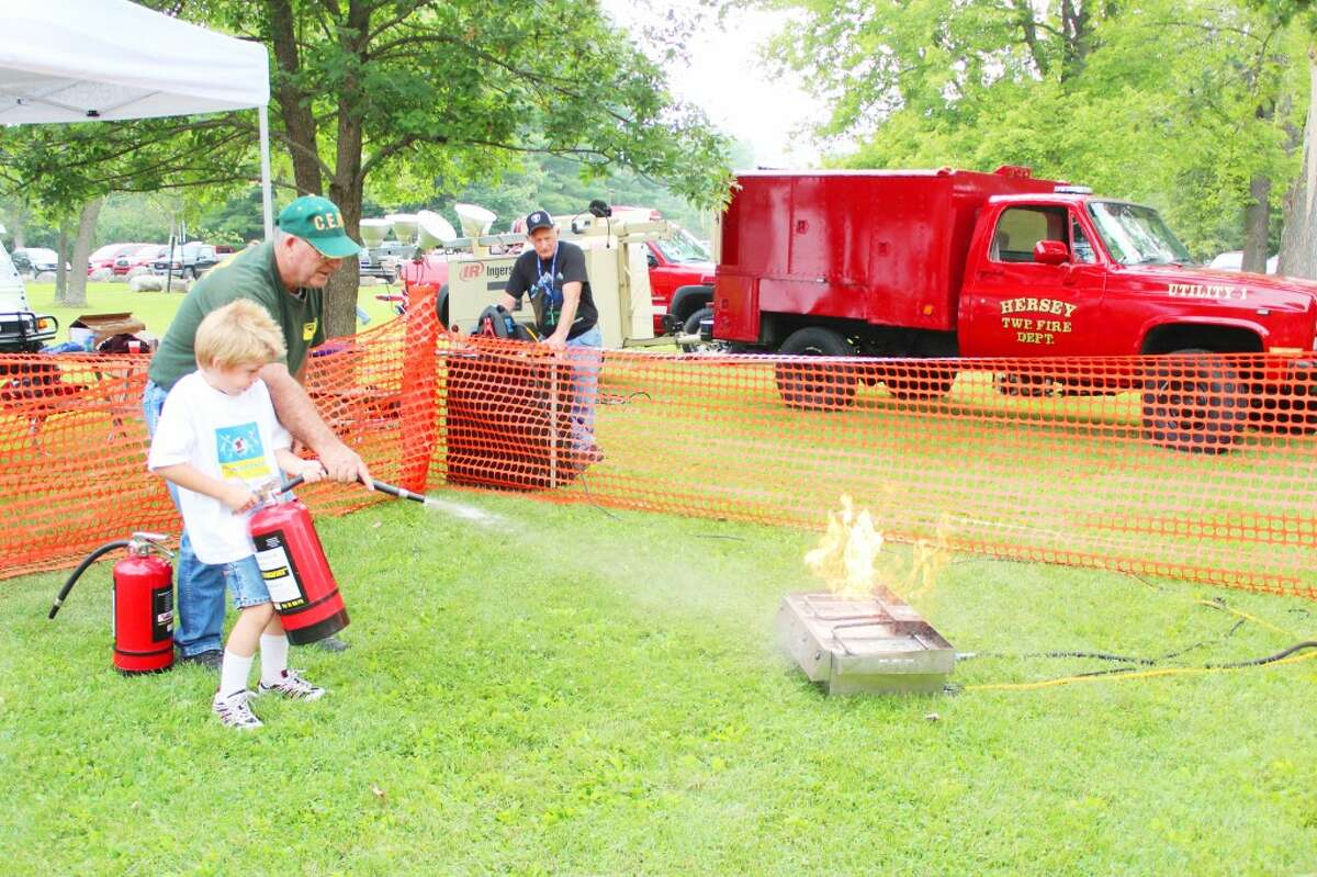Fire safety: A member of the Community Emergency Response Team teaches a child how to use a fire extinguisher during the Aug. 6 National Night Out event in Evart.