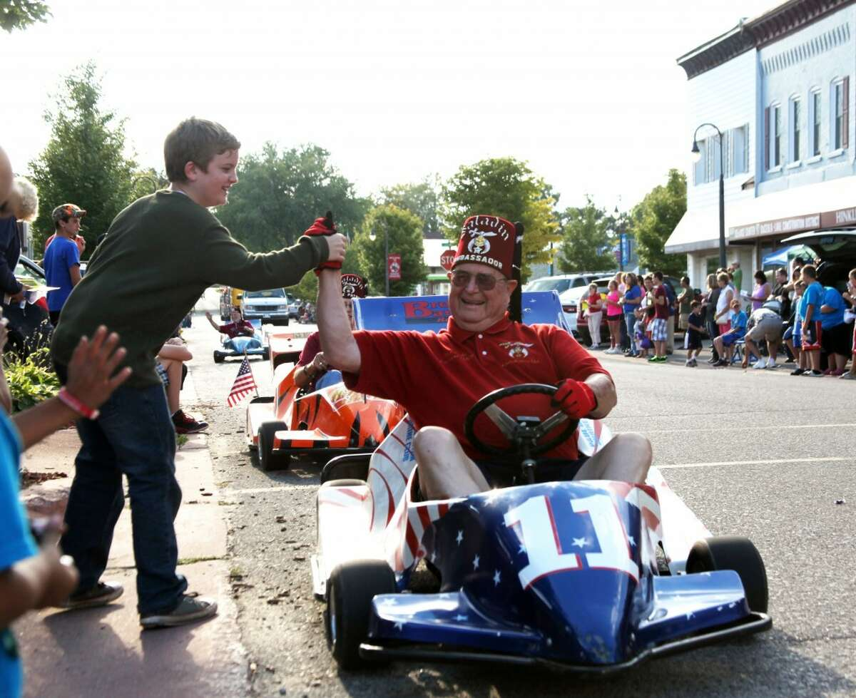 COMMUNITY CROSSROADS: Colby Perez (left) reaches out to a Shriner in the Crossroads Celebration parade in Reed City on Friday.