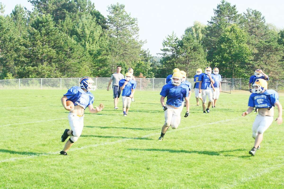 getting ready: Evart football players work on a running play Monday during practice. (Herald Review/John Raffel)