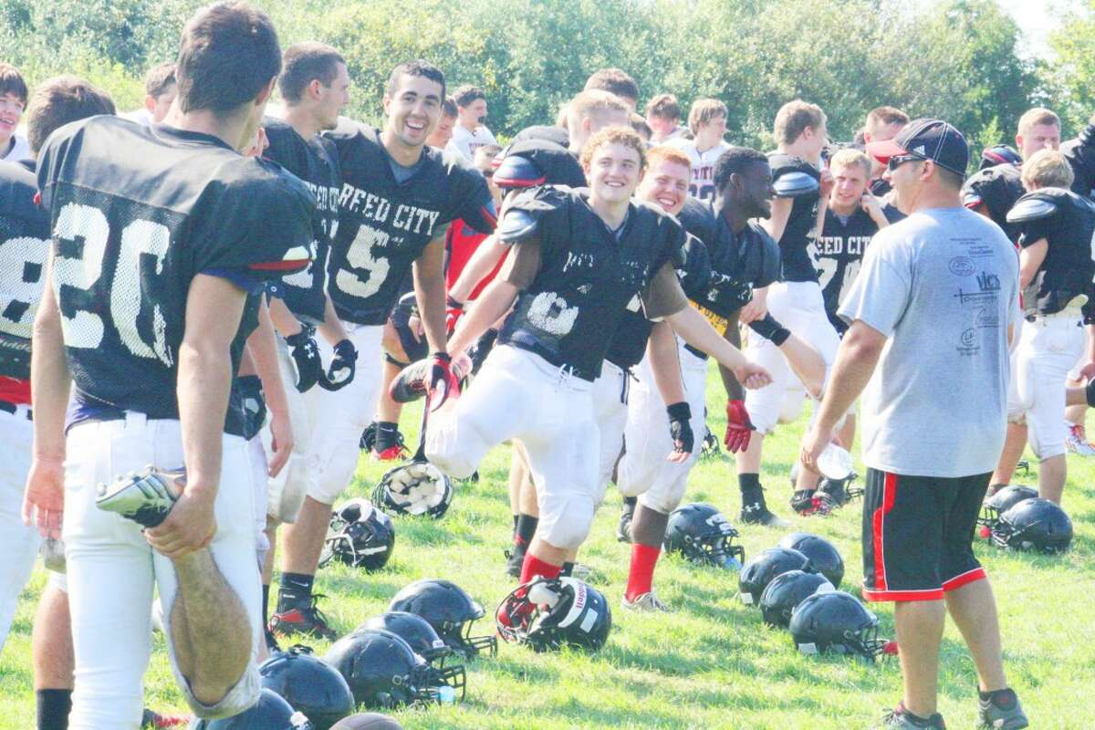 Reed City football players share a few laughs prior to practice but it's all business moments later during Monday workouts. (Herald Review/John Raffel)