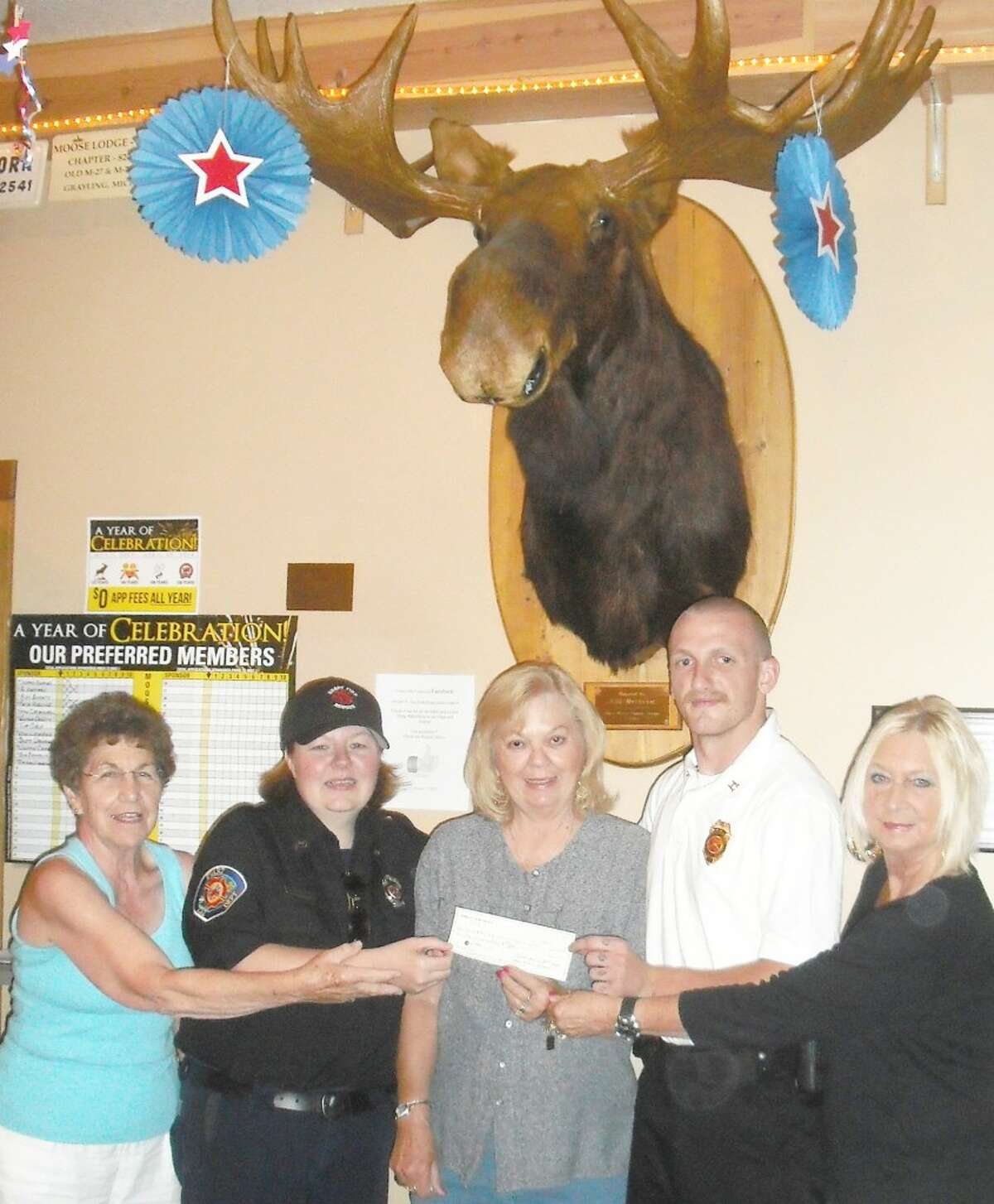 auction: Carol Roberts,chairman of the annual Moose Pie Auction; Tonya Swinehart, an EMT and the lead female Explorer advisor;Sandy Green, senior regent of the Women of the Moose; Jesse Hyden, former FireExplorer and current captain Evart Fire Department andArlene Henry, pie auction contributor, pose with a check donation of $200 given fromMoose Lodge No. 2452.(Courtesy photo)