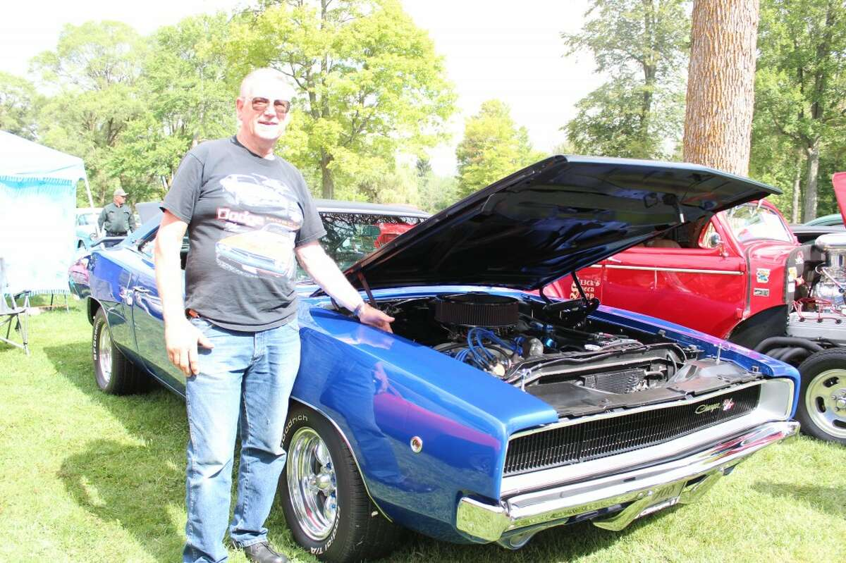 """Ed Rousseau, of Clare, stands next to his 1968 Dodge Charger at the Evart Car Show that took place on Aug. 31. Rousseau started attending the show 10 years ago and said the Charger, in the color """"electric blue pearl,"""" is his dream car."""