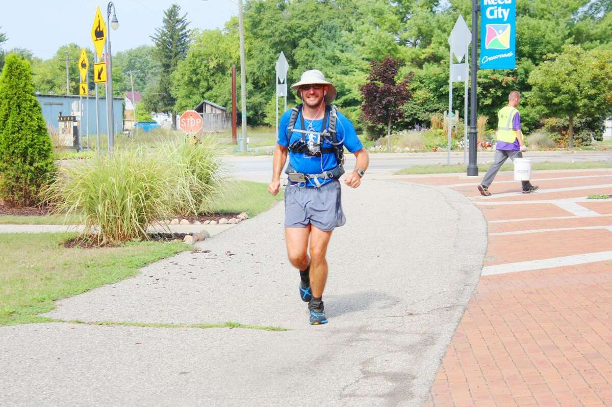 Across the Country: Tuscon native Brian Stark, 41, runs along the Pere Marquette Trail in Reed City on Thursday to reach a break point at the Reed City Depot. Stark has been running across Wisconsin and Michigan to further reach his goal of running through all 50 states. After staying the night in Baldwin, he continued onward through Lake and Osceola counties. His ending point will be in Bay City. (Herald Review photo/Karin Armbruster)