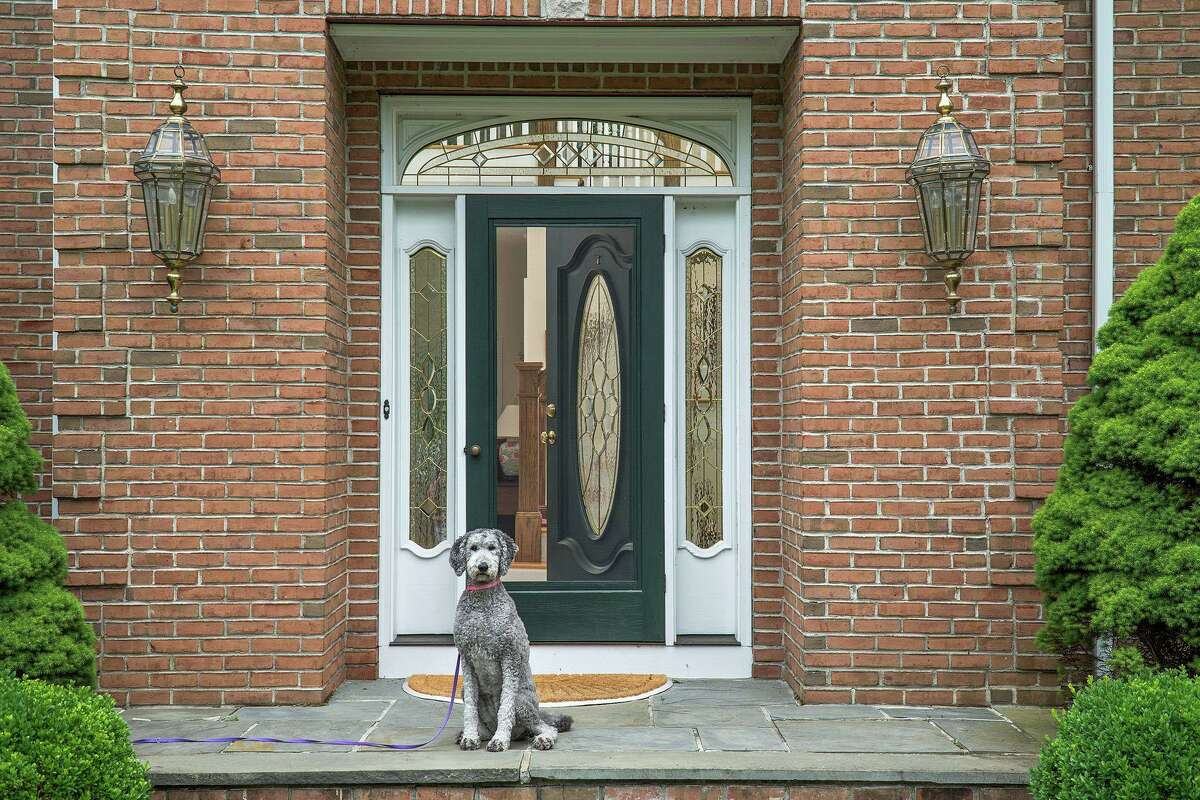 The entrance of this red brick house features a door with a decorative oval window framed by sidelights and a transom.