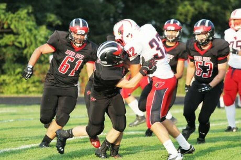 STOUT DEFENSE: Big Rapids running back Jon Spicer (32) is stood up after a short gain while Reed City's Ian MacDonald (61) and Issac Zolman (63) prepare to provide help in the Coyotes' 39-26 win on Friday. (Pioneer photo/Greg Buckner)