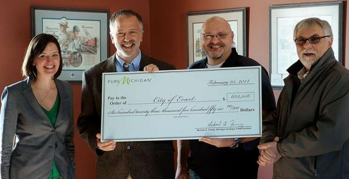 GRANT AWARD: (from left) Karen Keena presents Evart DDA Director Al Weinberg, Evart Mayor Eric Schmidt and Evart City Manager Zack Szakacs (Courtesy photo)