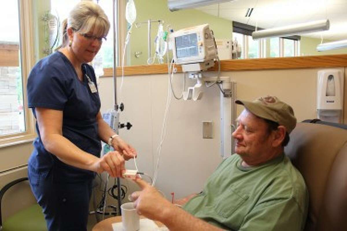 patients: Renee Leonard (left), a nurse at the Susan P. Wheatlake Regional Cancer Center, assists patient Gary Clementshaw, of Reed City, as he receives infusion therapy. Clementshaw said the staff and nurses at the facility are kind and helpful to each patient who walks through the building door. (Herald Review photo/Karin Armbruster)