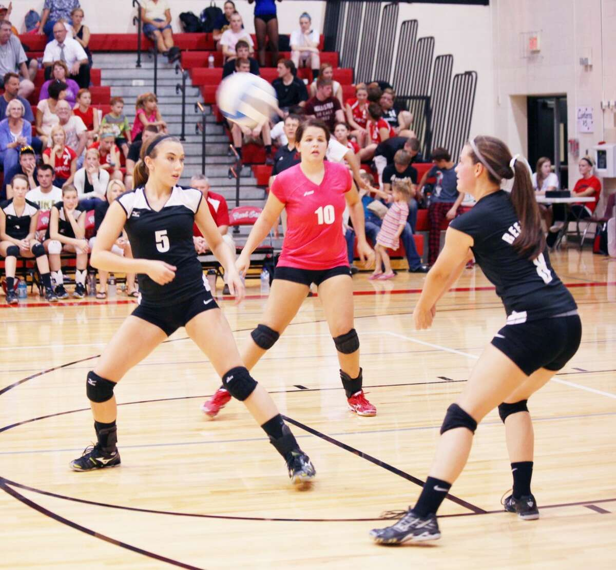 Reed City's Kayla Davis (riight) hits a shot while Karah Hensel (10) and Jacolyn Mullins prepare to react in last week's match against Morley Stanwood. (Herald Review photo/Greg Buckner)
