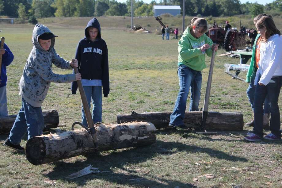 BACK IN TIME: Fifth graders from Reed City Area Schools took a trip to the Big Rapids Antique Farm and Power Club to learn how much work was involved to do things without the modern technology. Here, students find that moving logs with hooks is a lot of hard work. (Herald Review photo/Shannon Hartley)