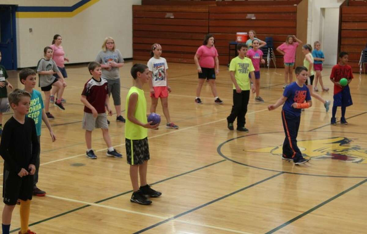 KEEP MOVING: Students participate in a game of dodgeball in the middle school gymnasium for their 60 minutes of physical activity. The program will host a variety of fitness activities during the program, such as bowling, roller skating, aerobics and more, to teach them there are many different ways to stay active.