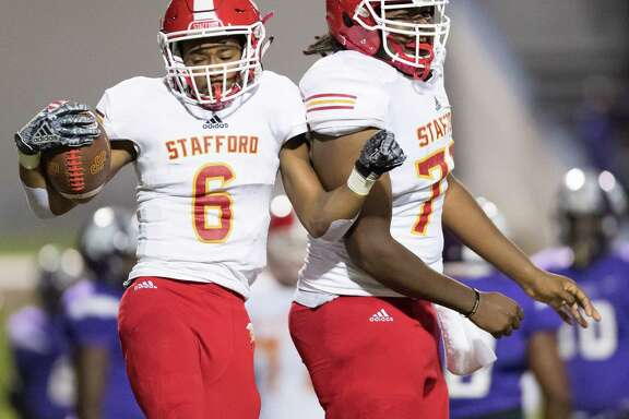 Jason Pamugo (6) of the Stafford Spartans celebrates his touchdown against the Wheatley Wildcats with Isaak Jose (75) in a high school football game on Thursday, October 11, 2018 at Barnett Stadium in Houston Texas.