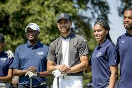 Howard University President Wayne Frederick, left, and Golden State Warriors guard Stephen Curry, center, pose for photographs with Howard student caddies before teeing off together at Langston Golf Course in Washington, Monday, Aug. 19, 2019, following a news conference where Curry announced that he would be sponsoring the creation of men's and women's golf teams at Howard University. (AP Photo/Andrew Harnik)