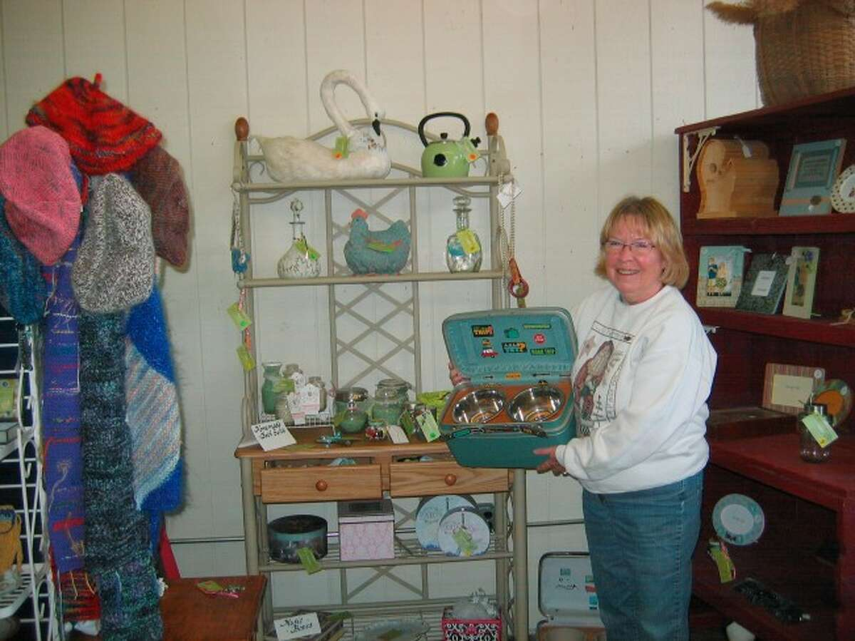 TO THE RESCUE: Renee Tolgo holds stylish carrier for dog bowls and toys fashioned from a vintage train case by Mary Lloyd. The store will carry those items and more, including oil and watercolor paintings, stained glass, jewelry, handbags, photography, pottery and knitted, embroidered and crocheted items.