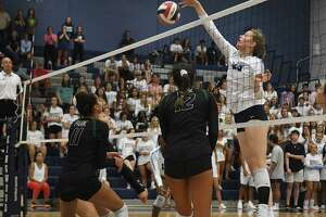 Kingwood's Megan Wilson, right, tips a ball at the net against Kingwood Park defenders Alia Williams (11) and Citialy Paz (12) during the 5th set of their non-district matchup at Kingwood High School on Aug. 16, 2019.