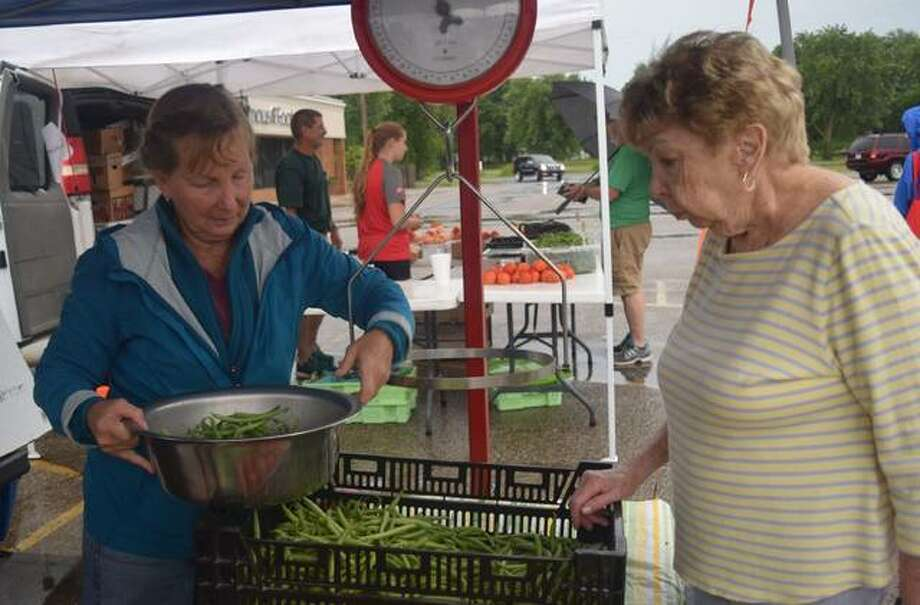Denise Smith, left, prepares green beans for sale for Barb Dunseth Saturday at the farmer's market in Jacksonville. Photo: Samantha McDaniel-Ogletree | Journal-Courier