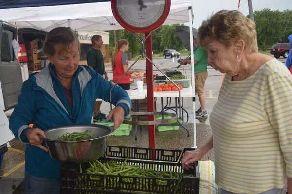 Denise Smith, left, prepares green beans for sale for Barb Dunseth Saturday at the farmer's market in Jacksonville.