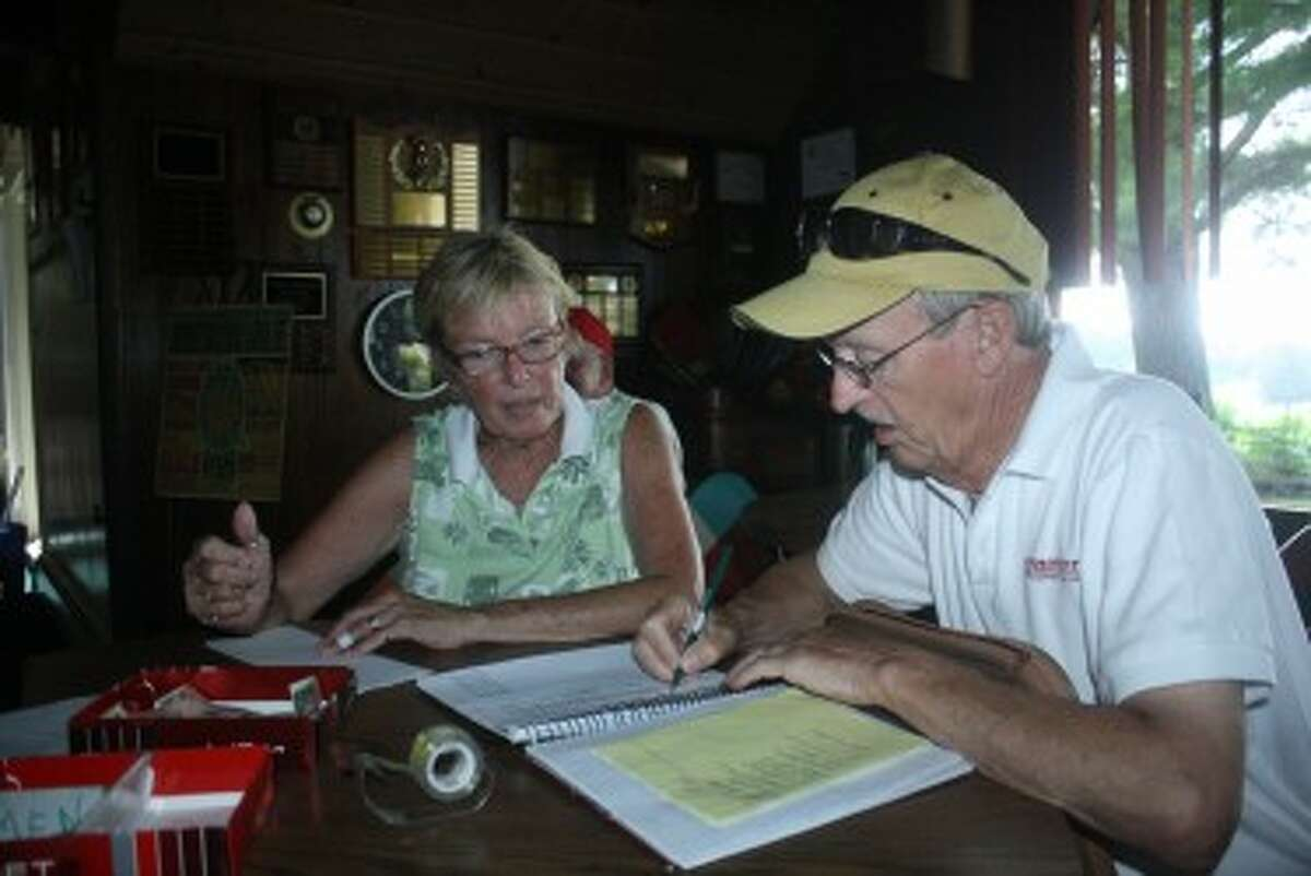 DOTTED LINE: Rex Knuth and Sharon McGreehan go over the paperwork Sunday prior to the start of the Mixed Scramble league at Spring Valley. (Pioneer photo/John Raffel)