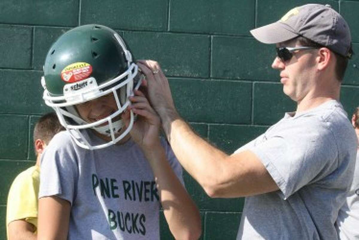 IN A SNAP: (ABOVE) Hunter Esiline, an eight-grader at Pine River, gets help from his dad, Todd Esline, in getting the helmet to fit at the Pine River football camp on Monday. (Pioneer photos/John Raffel)