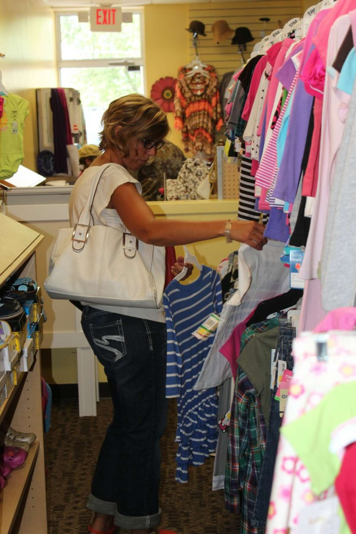 BARGAIN SHOPPING: Tanya Harrison looks through a rack of clothing at Nica's Boutique in Reed City. The store's name stands for New Inexpensive Clothing and Accessories as well as the end of owner Monica Fuller's name. (Herald Review photos/Sarah Neubecker)