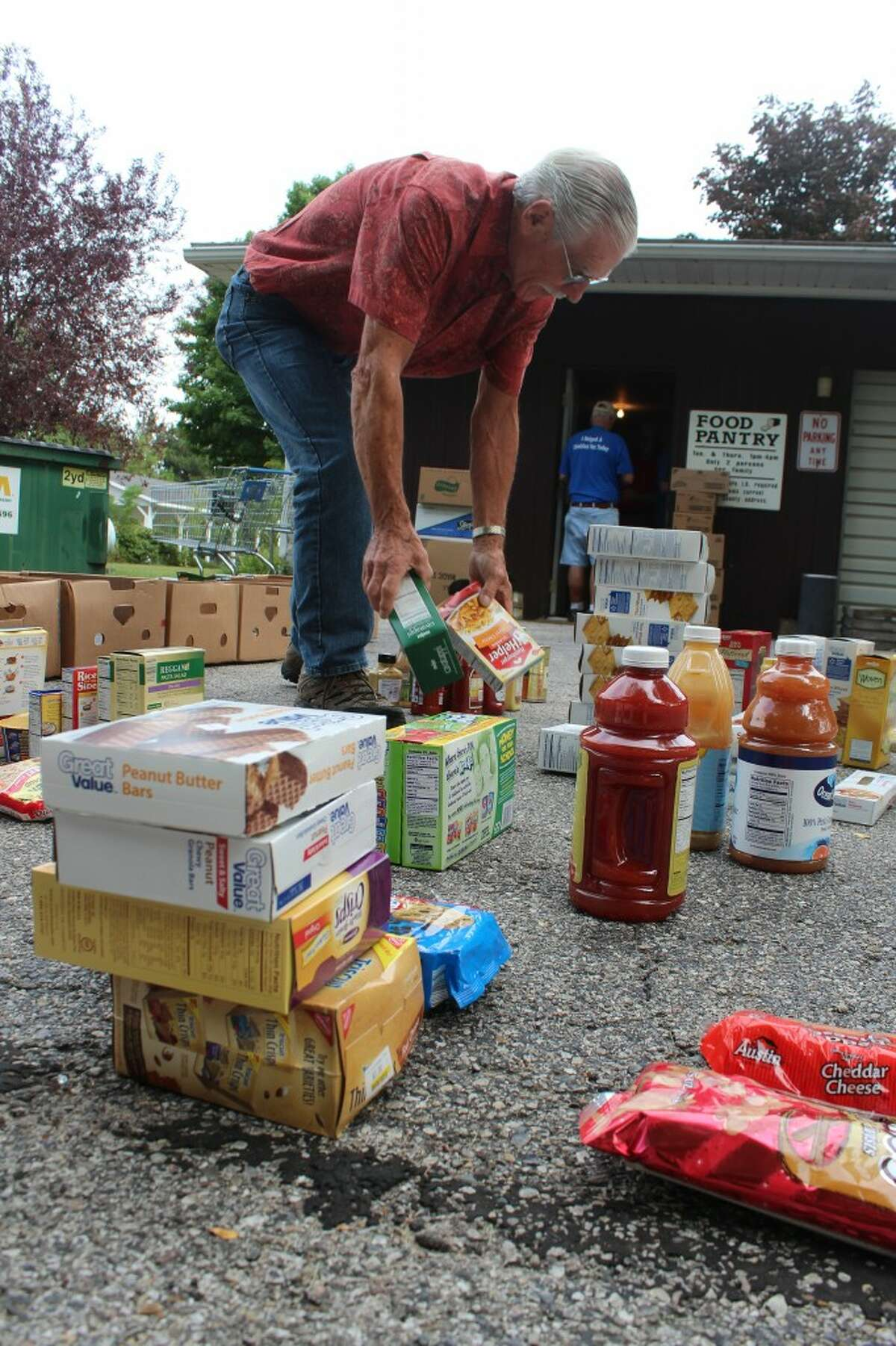 SORTING: Volunteer Russ Erbes sorts food items into piles after the pantry received a shipment from the Feeding America West Michigan Food Bank. The pantry is open from 1 to 4 p.m. on Tuesdays and Thursdays and is in need of donations.