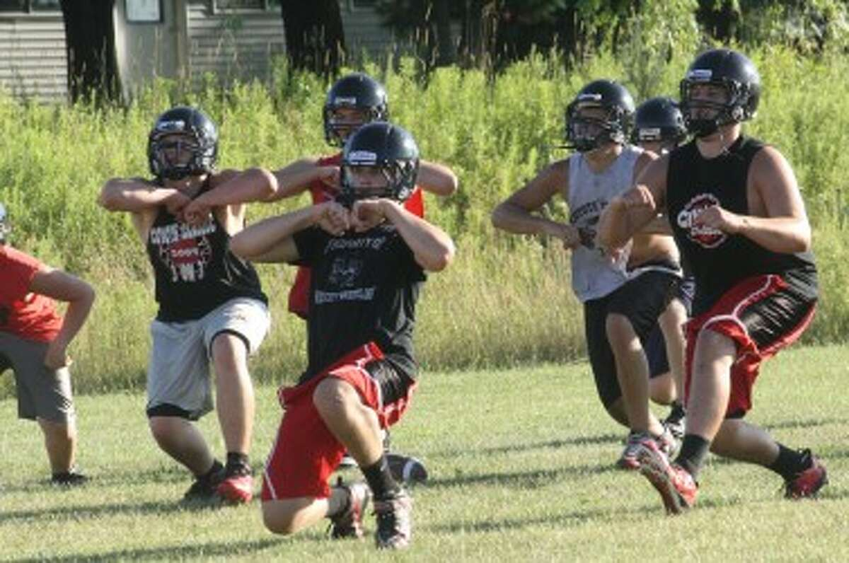 THROUGH THE MOTIONS: Reed City football players work on drills at last week's football camp. (Pioneer photo/John Raffel)