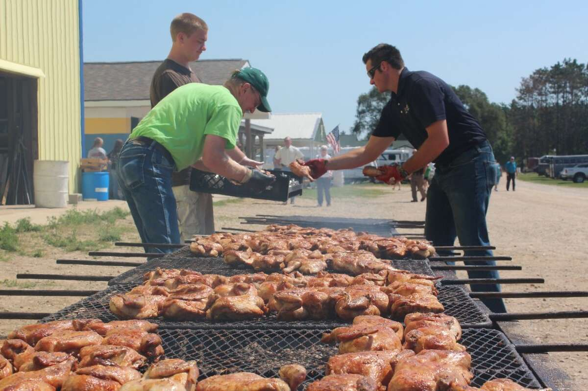 CHICKEN BARBECUE: Jerry Lindquist (left) and Dan Lee (right) fill a tray with barbecue chicken at the annual Farm Bureau chicken barbecue. Around 440 lunches were sold, raising around $2,200 for agricultural education. (Herald Review photos/Sarah Neubecker)