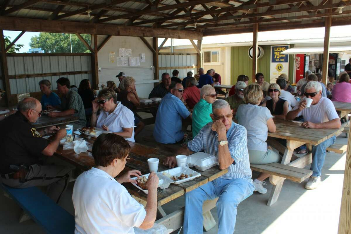 FAIR MEAL: Fair-goers enjoy a chicken lunch at the Farm Bureau chicken barbecue at the Osceola 4-H FFA Fair. The popular lunch has been served at the fair for around 50 years.