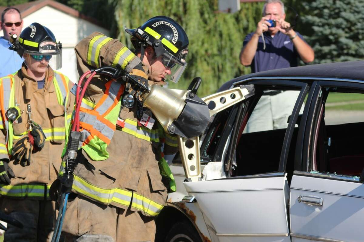 CLEAN CUT: A firefighter from the Reed City Fire Department uses a new hydraulic rescue tool to cut through a donated demo car during a practice exercise Tuesday. The new tools were purchased with a $16,000 AAA grant. (Herald Review photos/Sarah Neubecker)
