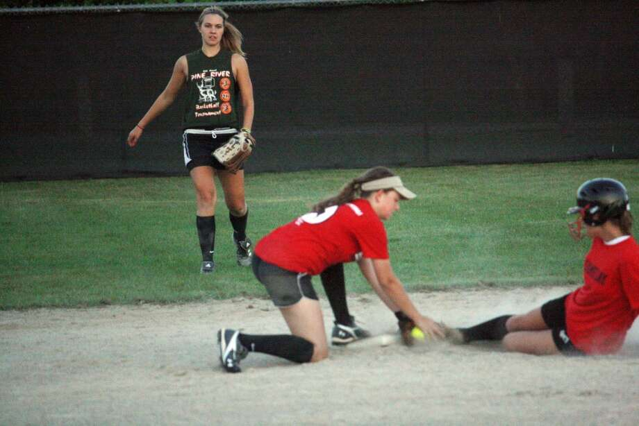 Taylor Steig of Reed City beats the tag of Pine River shortstop Nikita Oliver.