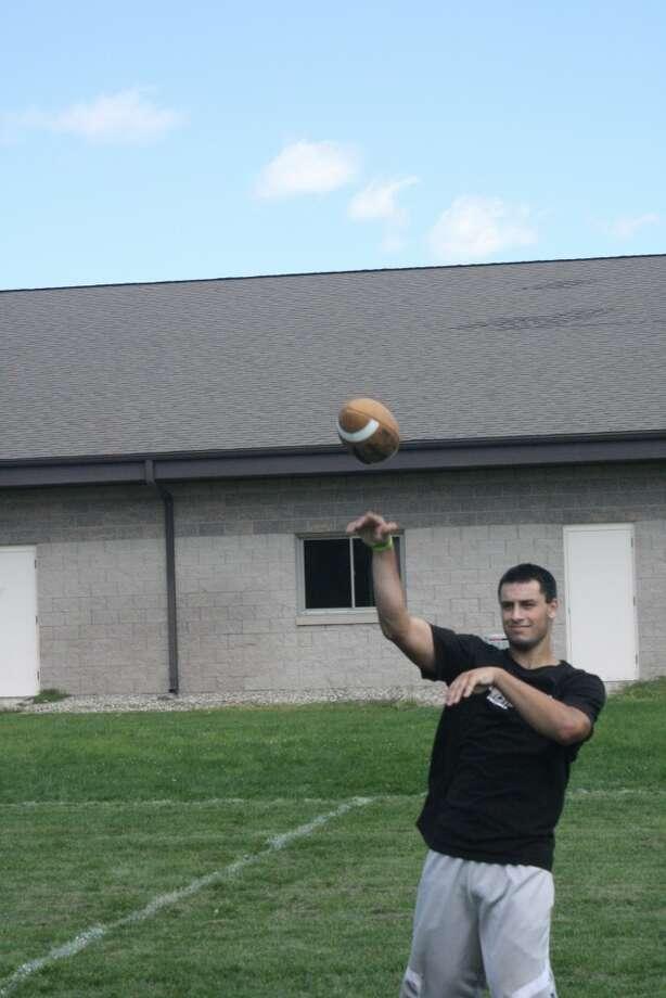 Austin Grein warms up his arm during an Evart football practice (Herald Review photo/John Raffel)