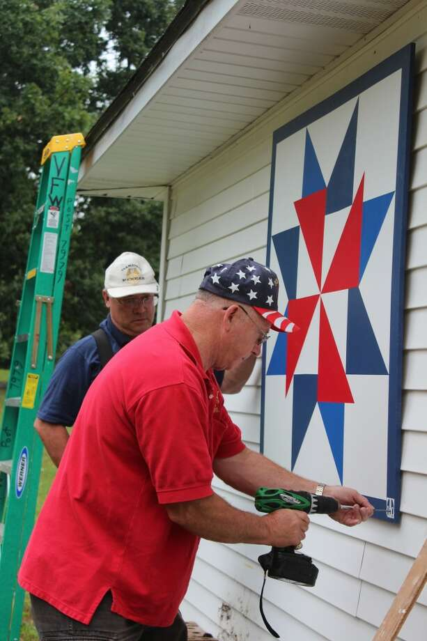 INSTALLATION: VFW member Dave Brickey drills in a screw to hold the new quilt block on the VFW post's storage shed while post commander Allan Rohen assists. VFW members and their families helped to paint the block.