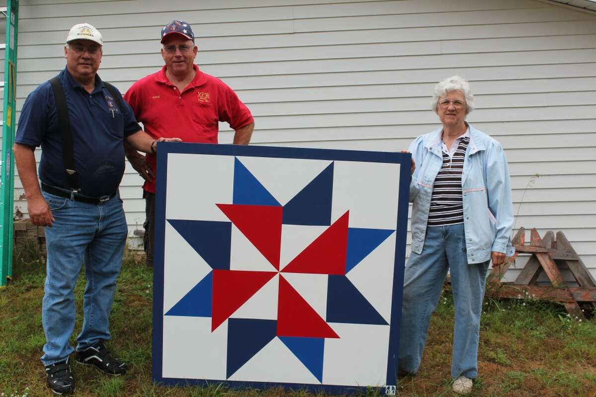 """PATRIOTIC MARKER: A quilt block painted in a pattern called """"America the Beautiful"""" was donated to the Evart VFW and AMVETS post by Nestle Waters. The block was installed on Aug. 9. Pictured is Allan Rohen, post commander; Dave Brickey, VFW member and Elsie Vredenburg, quilt trail founder. (Herald Review photos/Sarah Neubecker)"""