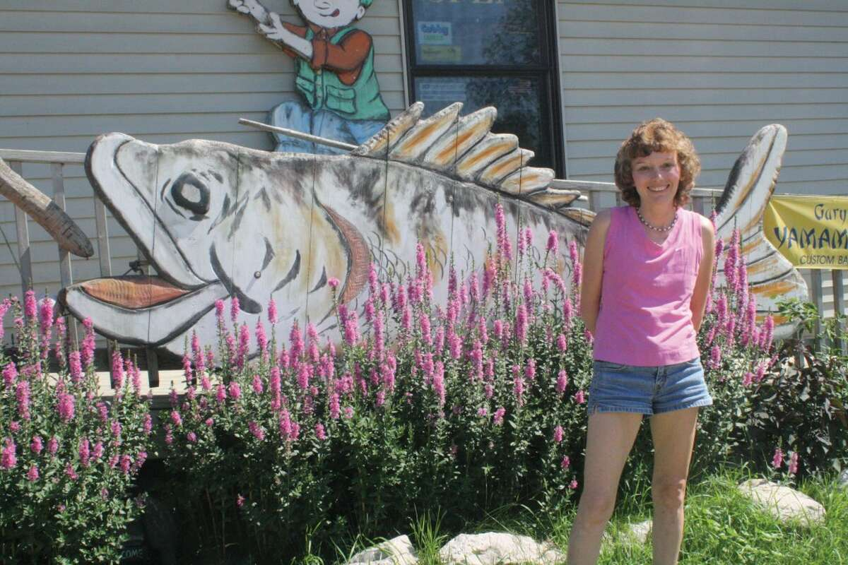 ALL ABOUT FISHING: Jolynn Hildrabridle stands in front of the Eyes Have It bait shop in Leroy. (Herald Review photo/John Raffel)