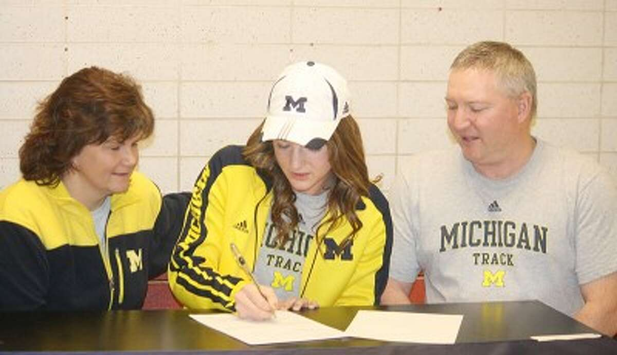 SIGNING ON: Sami Michell (center) signs her letter of intent to run track at the University of Michigan. (Pioneer photo/John Raffel)