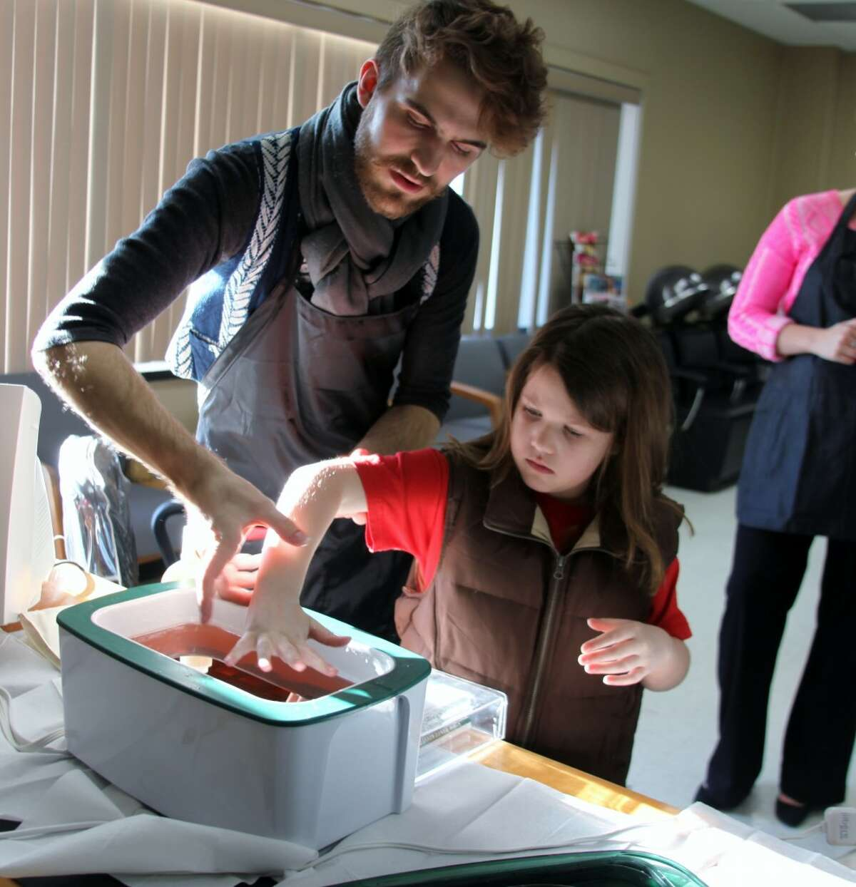COMMUNITY RESOURCE: Cosmetology student Timothy Sheffer guides Morgan Horvath, 7, through a wax dip at the MOCC open house.